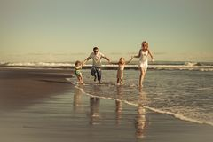 Happy family walking on the beach at the day time. Concept of friendly family on vacation Stock Photos