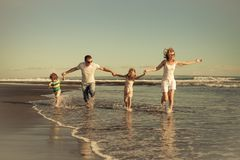 Happy family walking on the beach at the day time. Concept of friendly family on vacation Royalty Free Stock Image