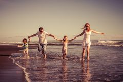 Happy family walking on the beach at the day time. Concept of friendly family on vacation Stock Photo