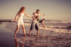Happy family walking on the beach at the day time. Concept of friendly family on vacation Royalty Free Stock Photos