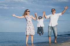 Happy family walking on the beach at the day time. Stock Photo