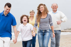 Happy family walking on the beach Stock Photo