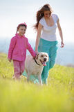 Happy family walking with dog. In green field Royalty Free Stock Photo