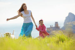 Happy family walking with dog. In green field Royalty Free Stock Images