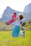 Happy family walking with dog. In green field Royalty Free Stock Photography