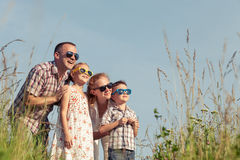 Happy family walking on the field  at the day time. Family having fun on the park. Concept of friendly family and of summer vacation Stock Image