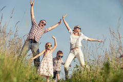 Happy family walking on the field  at the day time. Family having fun on the park. Concept of friendly family and of summer vacation Royalty Free Stock Photography
