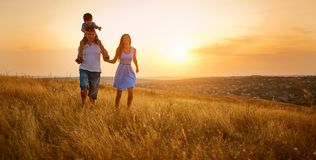 Happy family walking on field in nature at sunset.  stock photos