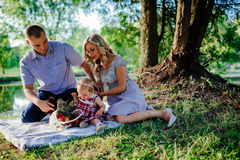 Happy family are walking in the green summer park. Picnic Stock Photo