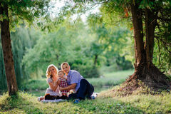 Happy family are walking in the green summer park Stock Images