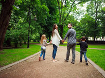 Happy family walking holding hands in green city park Stock Image