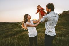 Happy family walking with infant baby outdoor. Mother and father parents lifestyle traveling summer vacations together royalty free stock image
