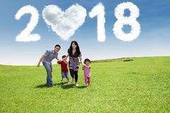 Happy family walking in the meadow. With clouds shaped heart and numbers 2018 in the sky Royalty Free Stock Images