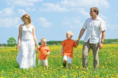 Happy family walking on meadow Stock Photography