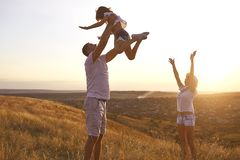Happy family walking in nature at sunset in summer. royalty free stock photo
