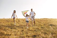 Happy family walking in nature at sunset in summer. stock images