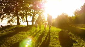 Happy family walking near the sea. Field and trees in countryside. Warm colors of sunset or sunrise. Loving parents and