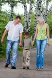 Happy family walking in the park. Holding hands and smiling Stock Photo