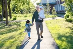 Happy family walking in park. father with two daughters at sunny day. dad with two little kids talking in park outdoor. Family authentic lifestyle portrait stock photos