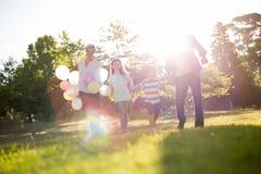 Happy family walking at the park. On a sunny day Stock Photos