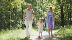 Happy family walking in the park at sunny day Stock Image