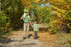 Happy family walking on the path. Father and his two children walking on the path during autumn Stock Images