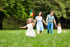 Happy family walking playing in the park.  Stock Photography