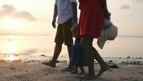 Happy family walking on sea coast. Holding a little girl by the hand on sunset. Daughter going into water stock footage