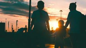 Happy family walking on sea coast. Silhouettes sunset. Slow motion. Happy family walking on sea coast. Silhouettes sunset stock video