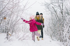 Happy family walking on the snowy woods Royalty Free Stock Images