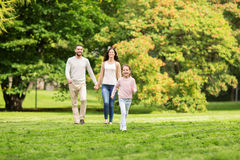 Happy family walking in summer park and having fun. Family, parenthood, adoption and people concept - happy mother, father and little girl walking in summer park Royalty Free Stock Photos