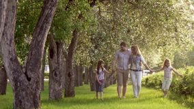 Happy family walking in summer Park near the blossoming Apple trees. father, mother and two daughters spend time
