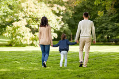 Happy family walking in summer park. Family, parenthood, adoption and people concept - happy mother, father and little girl walking in summer park Stock Images