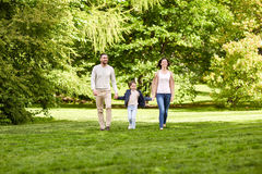 Happy family walking in summer park. Family, parenthood, adoption and people concept - happy mother, father and little girl walking in summer park Stock Photo