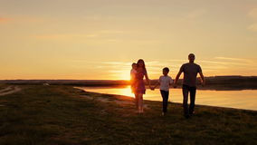 Happy family walking at sunset near the water. stock footage