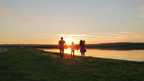 Happy family walking at sunset on the sea in summer stock video