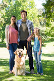 Happy family walking their dog in the park Stock Photography