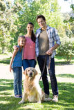 Happy family walking their dog in the park. On a sunny day Stock Photography