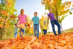 Happy family walking together holding hands. Big happy family walking together holding hands in a row in the park during beautiful sunny autumn day Royalty Free Stock Images