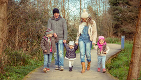Happy family walking together holding hands in the. Happy family walking together holding hands over a wooden pathway into the forest Royalty Free Stock Photography