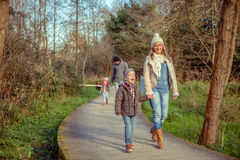 Happy family walking together holding hands in the. Happy family walking together holding hands over a wooden pathway into the forest Stock Photos