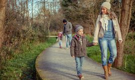 Happy family walking together holding hands in the forest. Happy family walking together holding hands over a wooden pathway into the forest Royalty Free Stock Photography