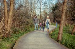 Happy family walking together holding hands in the forest. Happy family walking together holding hands over a wooden pathway into the forest Stock Photo