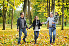 Happy family walking together in a park Royalty Free Stock Images
