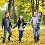 Happy family walking together in a park. Happy family walking together in an autumn park Royalty Free Stock Image