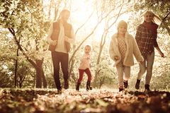 Happy family walking trough park together with open arms. Happy smiling family walking trough park together with open arms stock photo