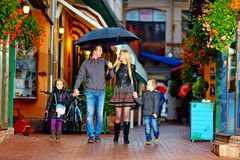 Happy family walking under the rain on colorful street Royalty Free Stock Images