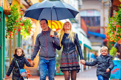 Happy family walking under the rain on colorful street Stock Photo