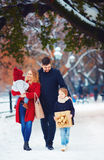 Happy family walking on winter street at holidays. Happy family of four  walking on winter street at holidays Royalty Free Stock Image