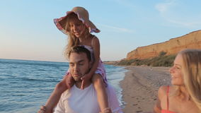 Happy family walks along the seashore stock footage
